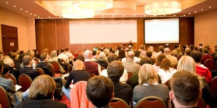 Rear view of many listeners sitting on chairs during lecture at conference